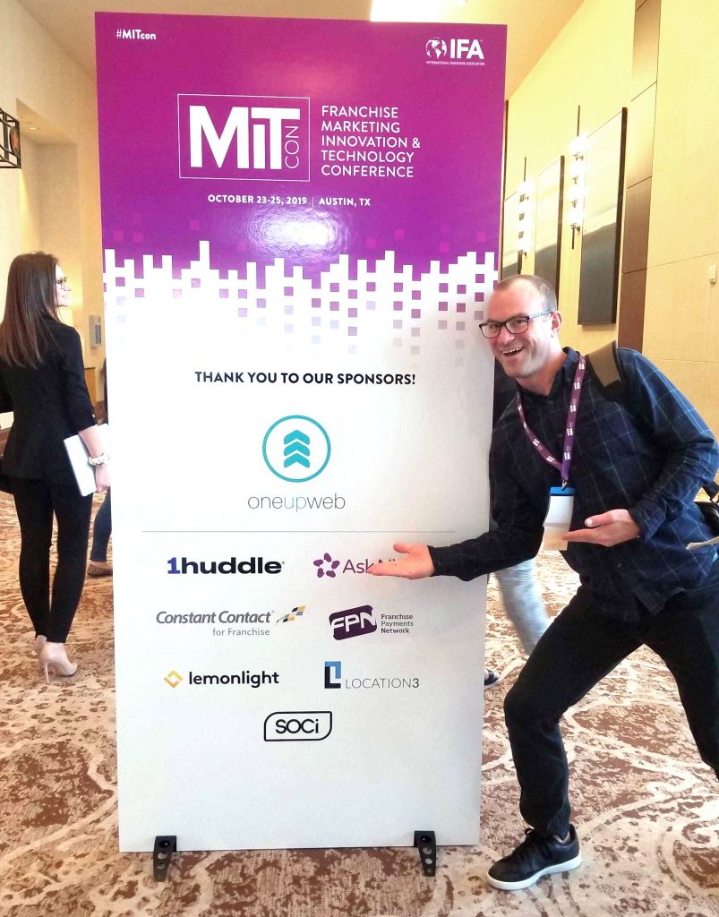 freddy hunt in front of a banner at mitcon