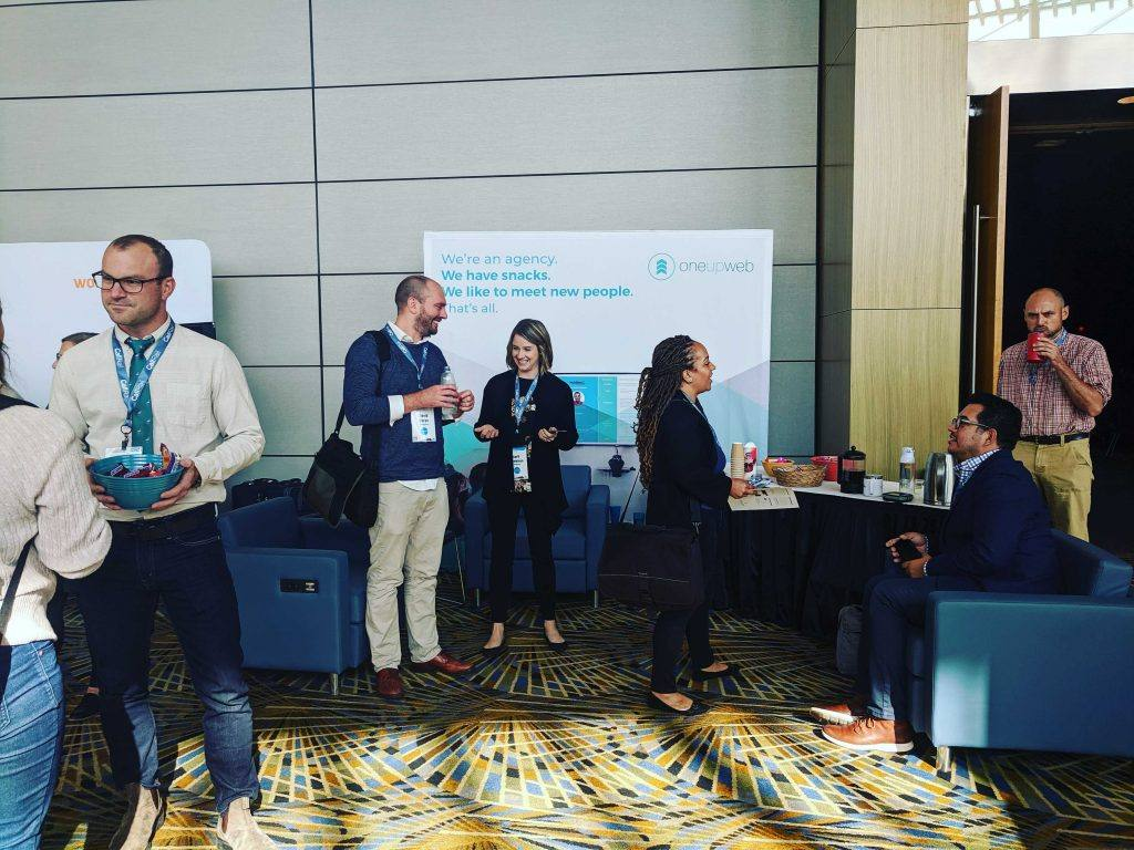 the oneupweb booth at digital summit detroit with team members learning and networking.