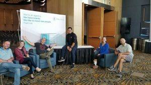 group of people sitting in front of oneupweb sign at conference booth