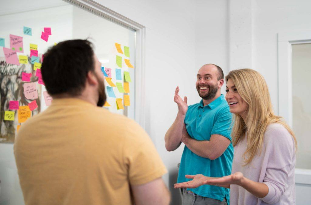 Three people having an exciting conversation while planning marketing strategies with sticky notes on the wall