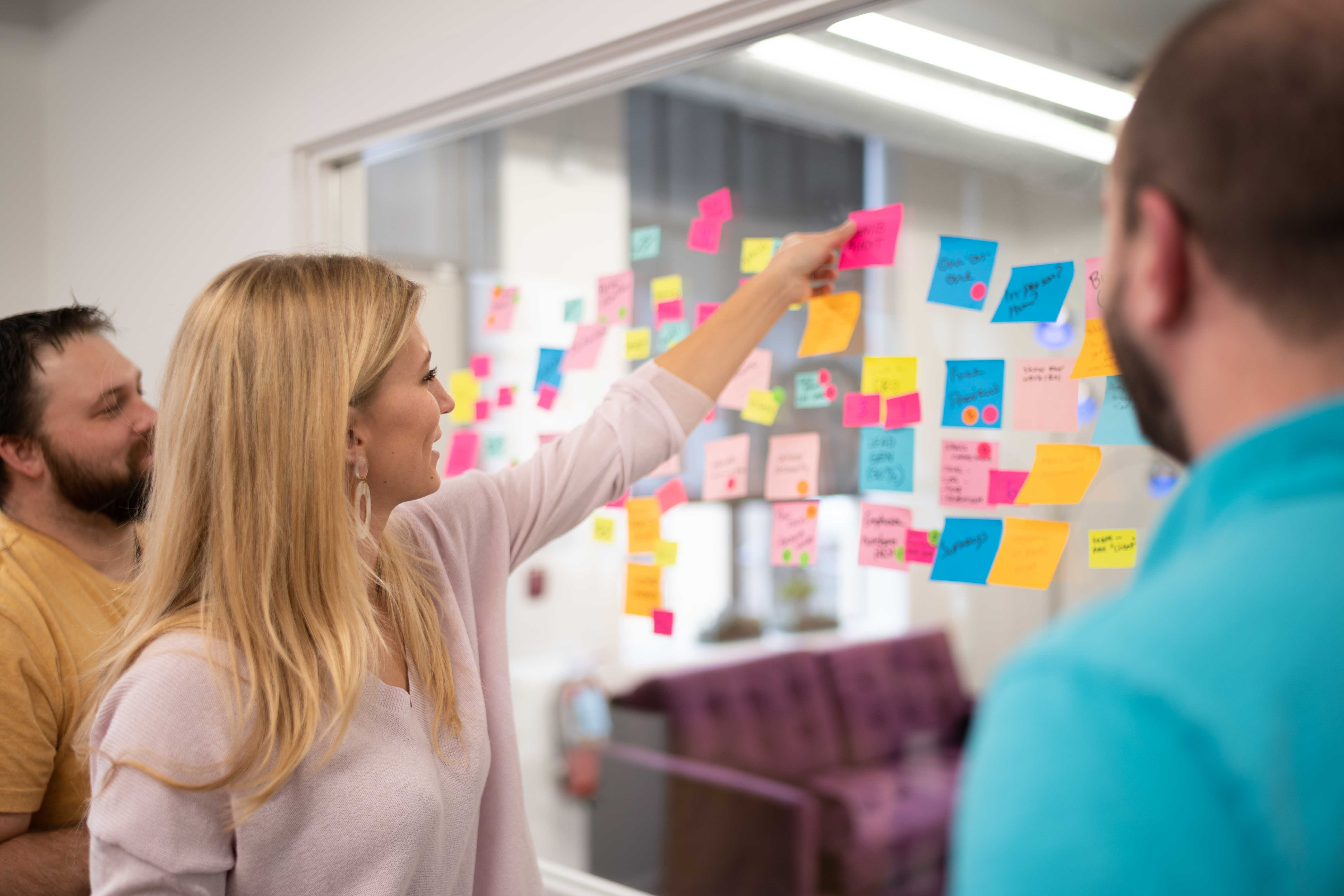 Three coworkers gathered around a wall of post-it notes. girl sticking a note on the wall and contributing to brainstorming session