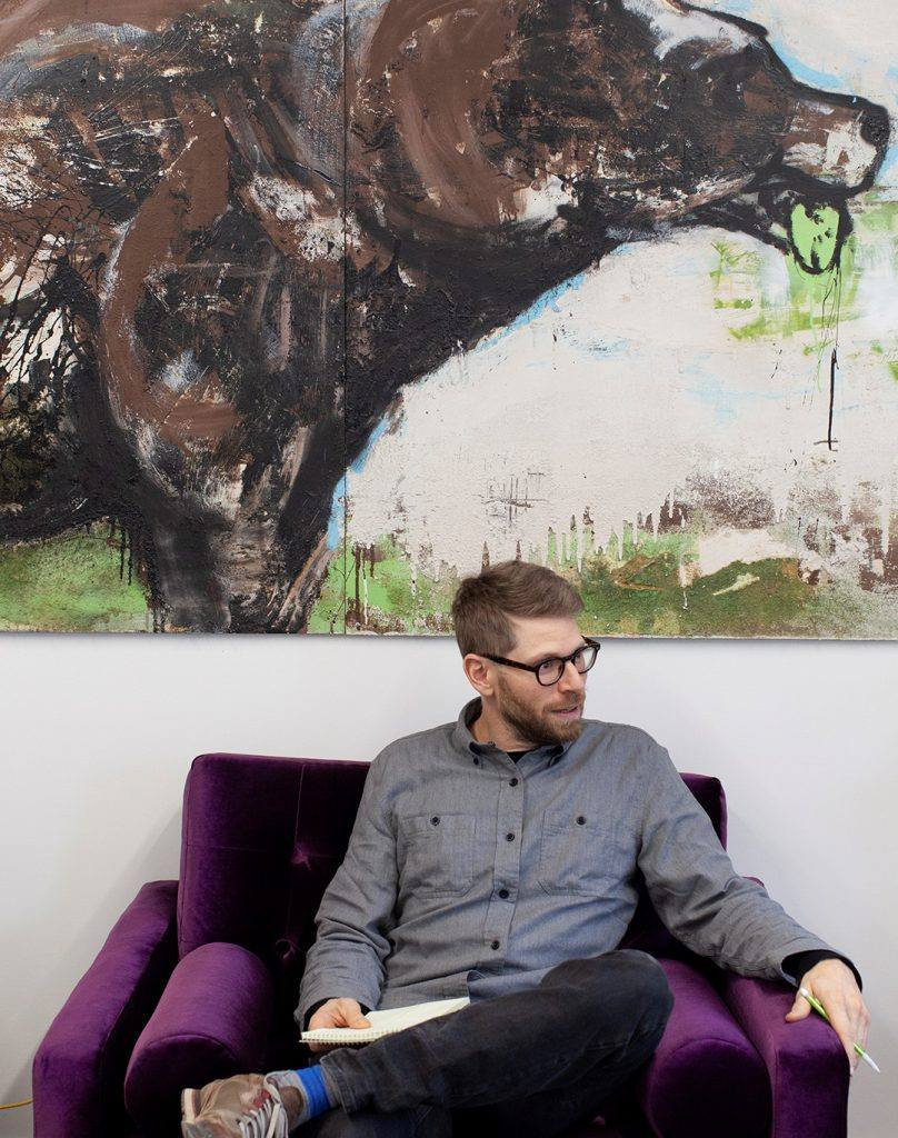 Man sits in an armchair with a notebook in front of a large painting of a bear