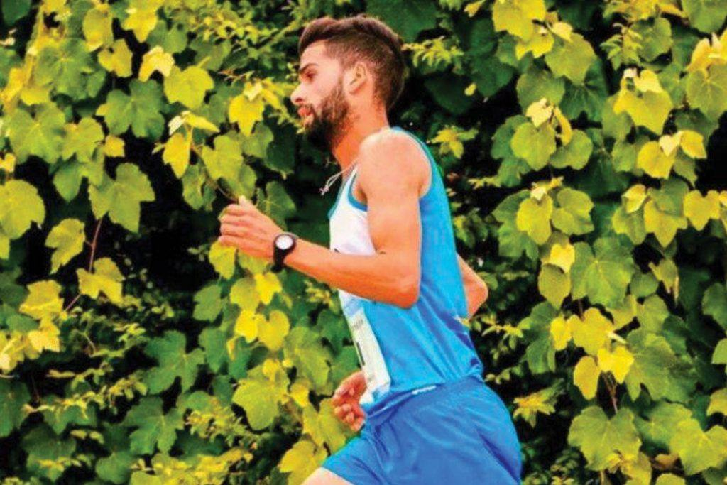Young man in Brooks running outfit runs past a vine-covered wall
