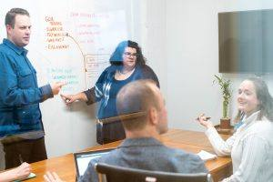 Oneupweb employees discuss market research and write notes on a whiteboard wall