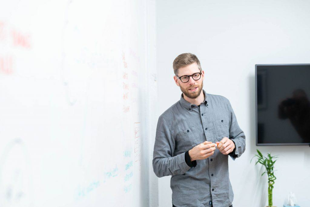 Professional man holds dry erase marker in meeting room
