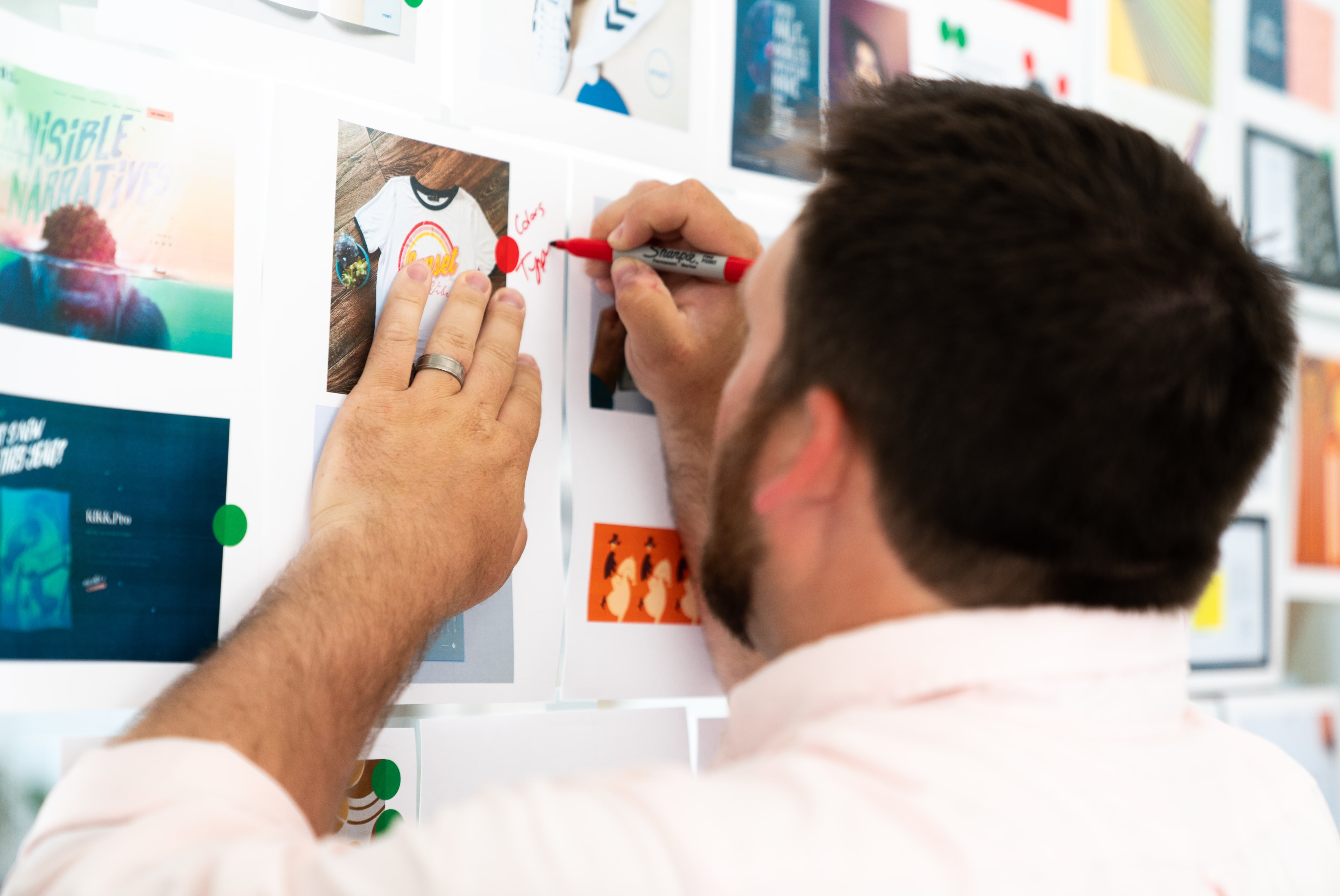 Designer writes notes on printed images tacked to a wall for a brand style guide