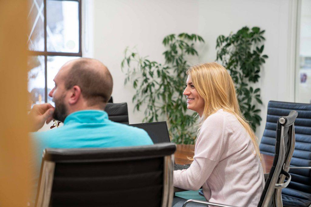 Two marketing employees watch a presentation