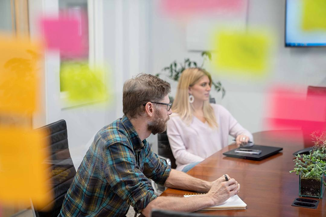 Two marketing experts discuss process, with sticky notes in the foreground