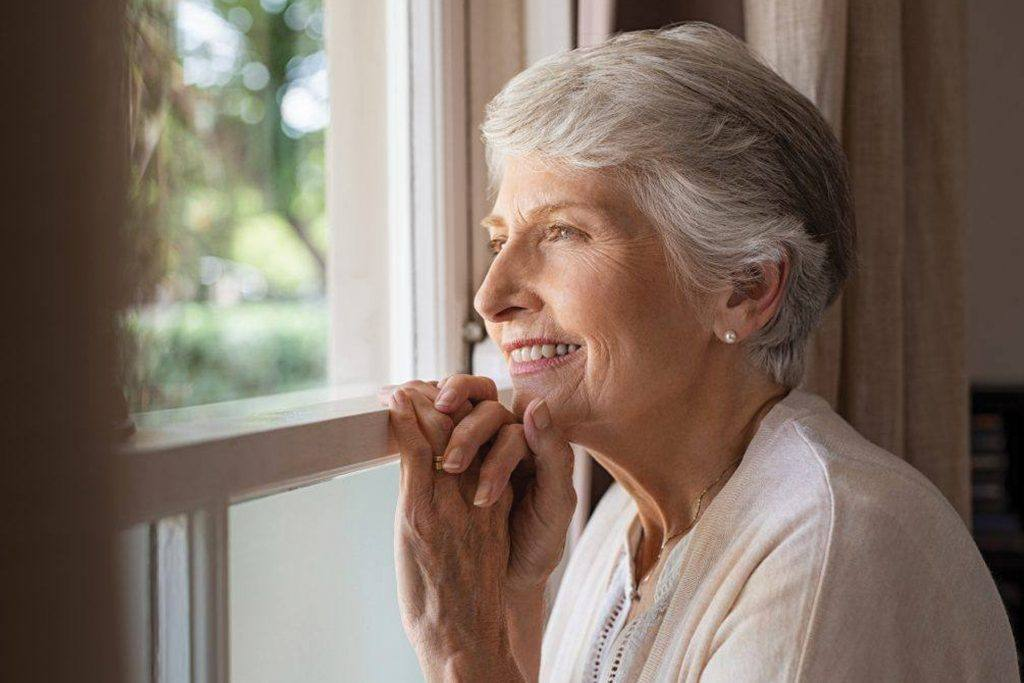 An older woman with gray hair smiles while looking out a window and resting her head on her hands