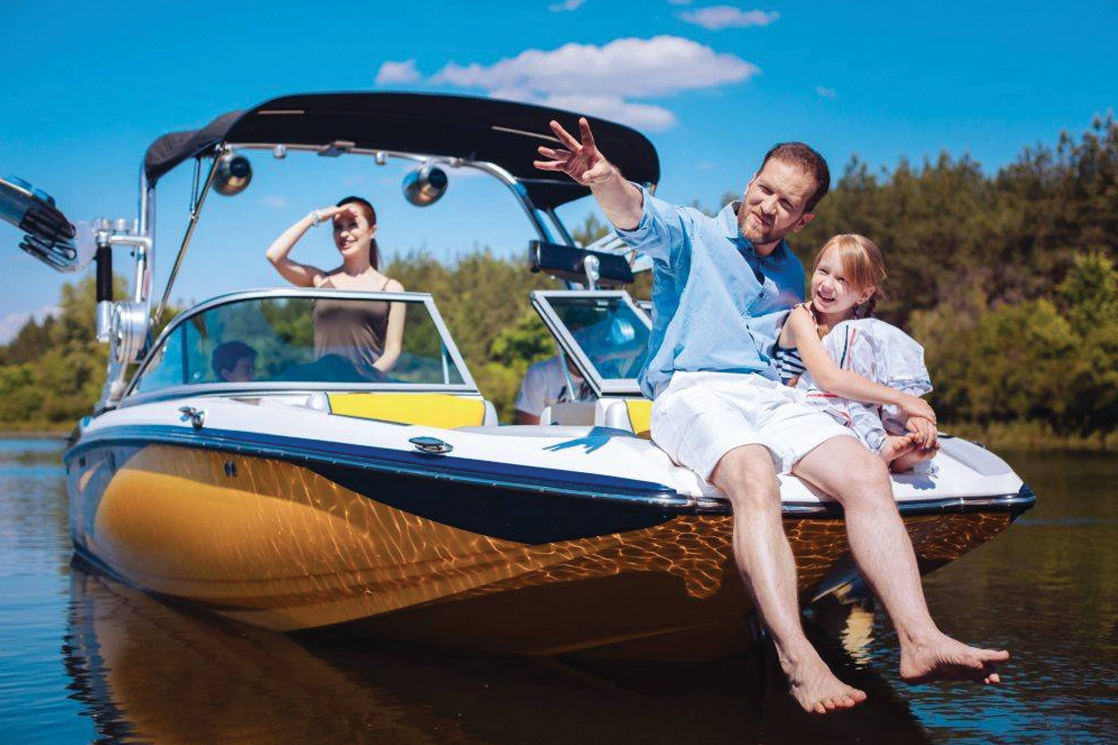 Man, woman, and child relax on a luxurious speedboat with a sunshade