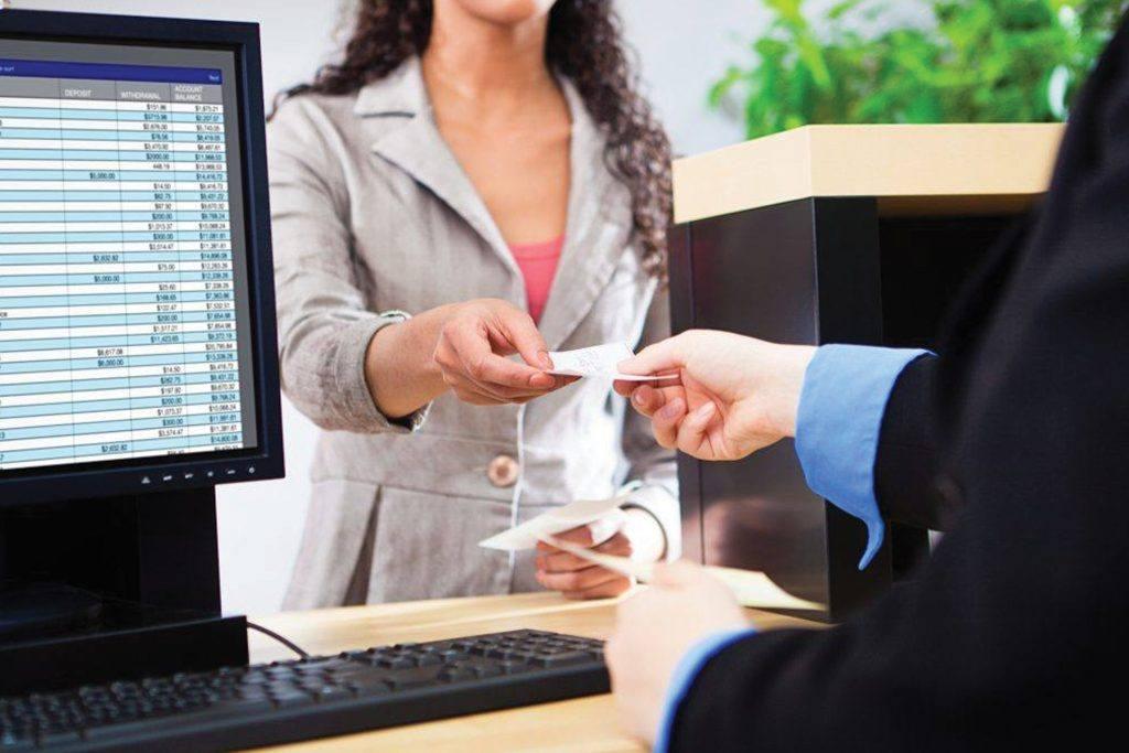 Bank teller hands customer a receipt