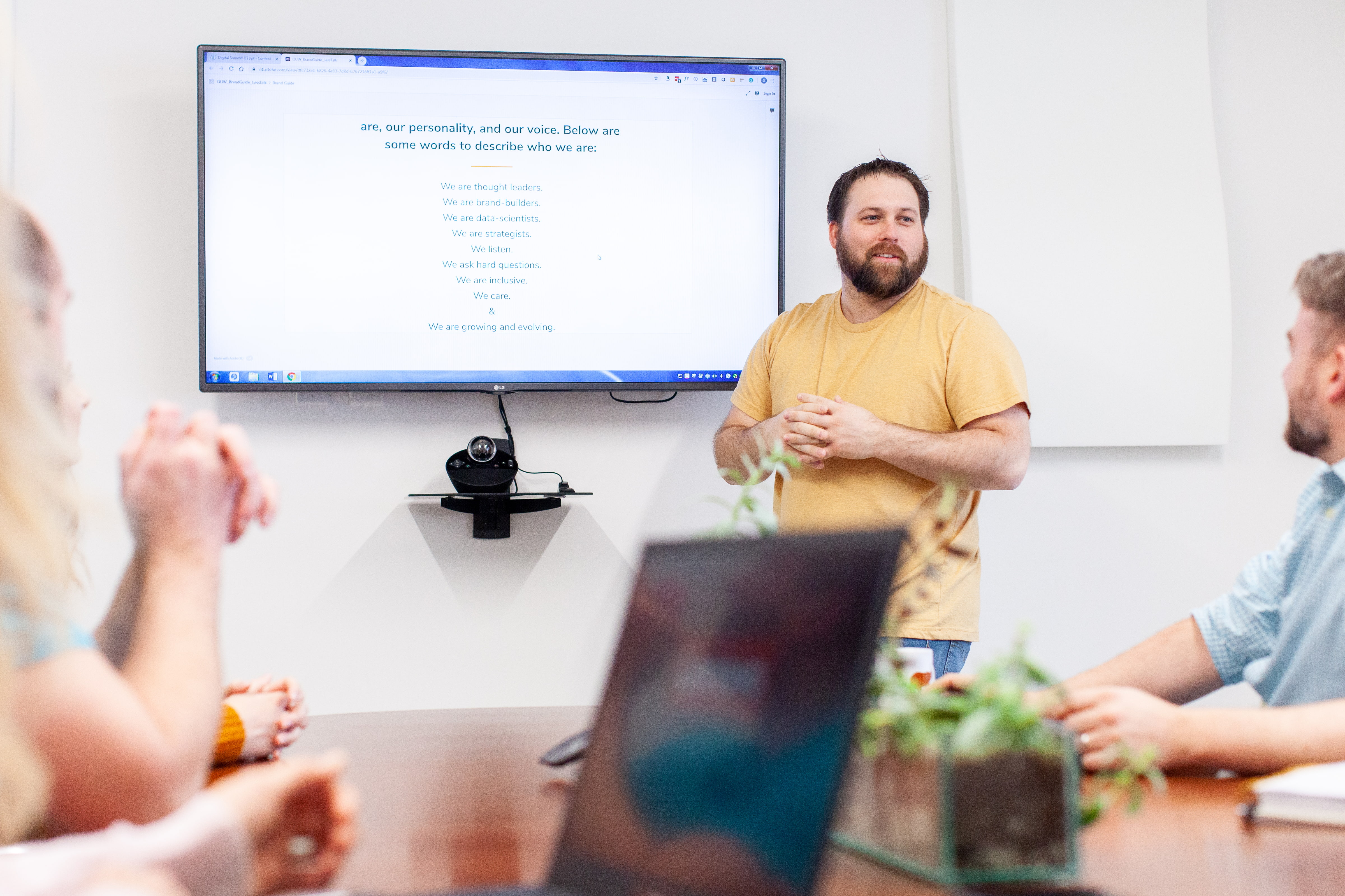 Man making a marketing and branding presentation to a conference room of people.