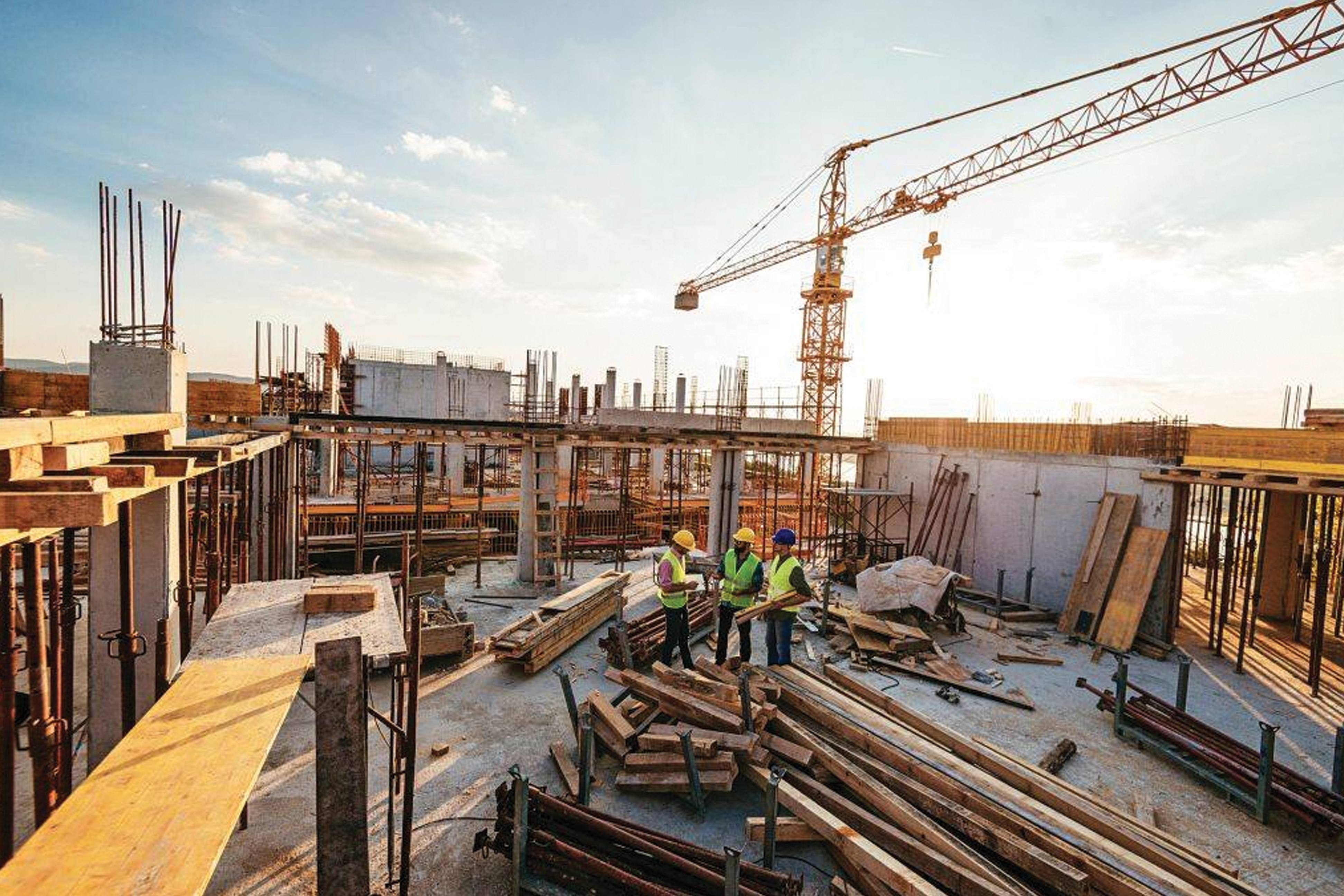 Three construction workers talk on a job site, surrounded by lumber, half-finished walls, and a crane