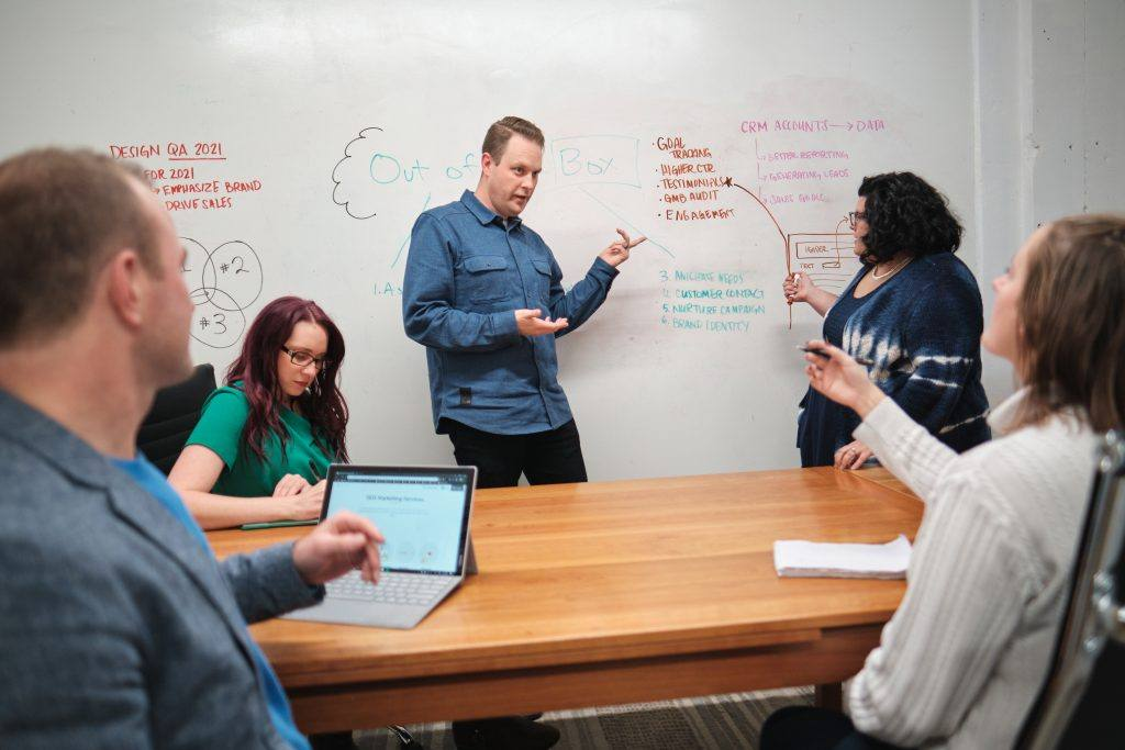 Marketing experts gather around a table and a whiteboard wall to discuss strategy