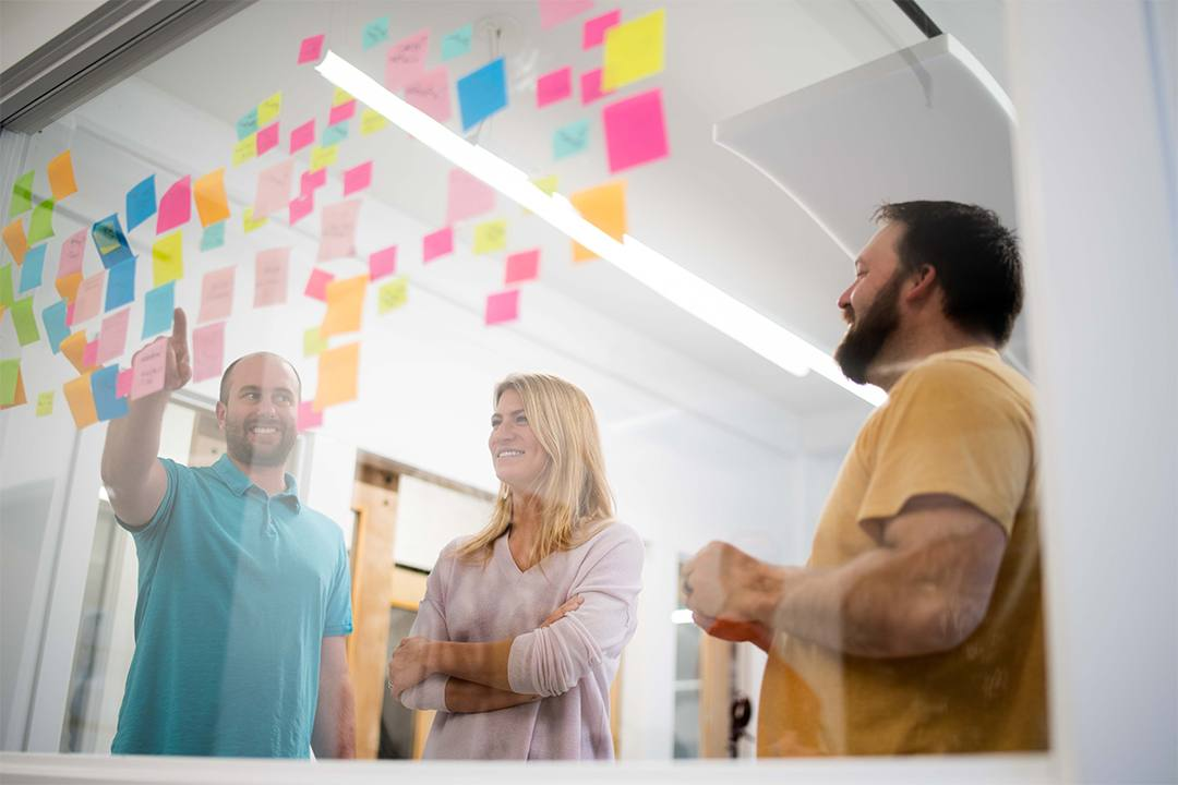 a man, woman and another man, part of oneupweb digital marketing team, go through a creative meeting exercise with post-it notes on the glass