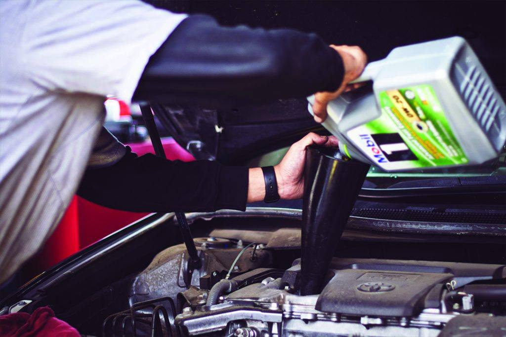 a man adds oil to a car's engine