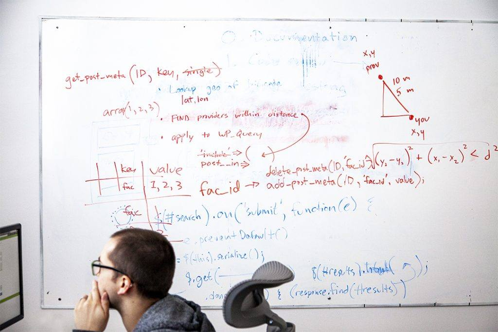 Website developer works on his computer while notes from a team brainstorm are still on the whiteboard behind him