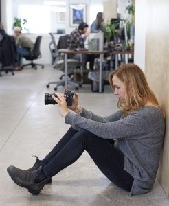 oneupweb videographer emily tewers composes a shot with her camera while sitting on the ground