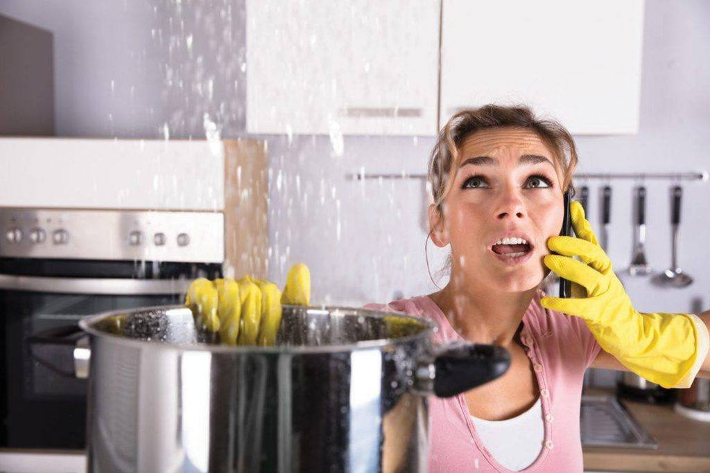 Worried woman talks on phone and holds a large cooking pot to catch water that's leaking from her ceiling