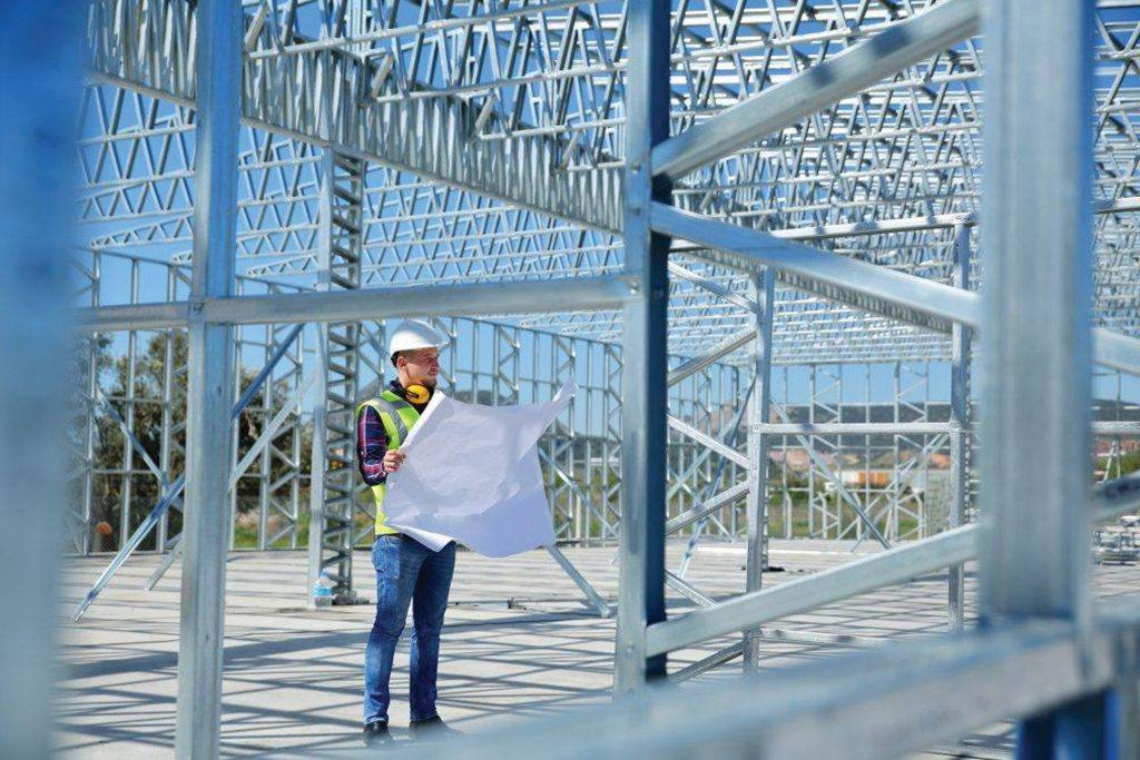 A construction worker holds a blueprint and stand beneath steel framing for a new building