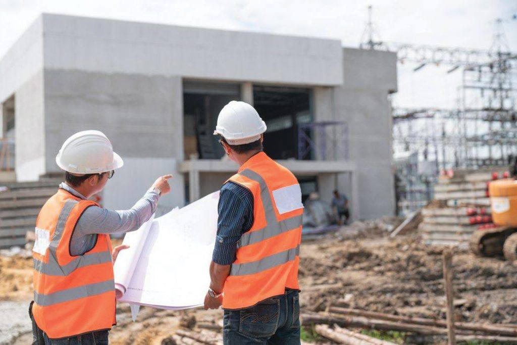 Two McCarthy construction engineers review a blueprint and point at an unfinished concrete building