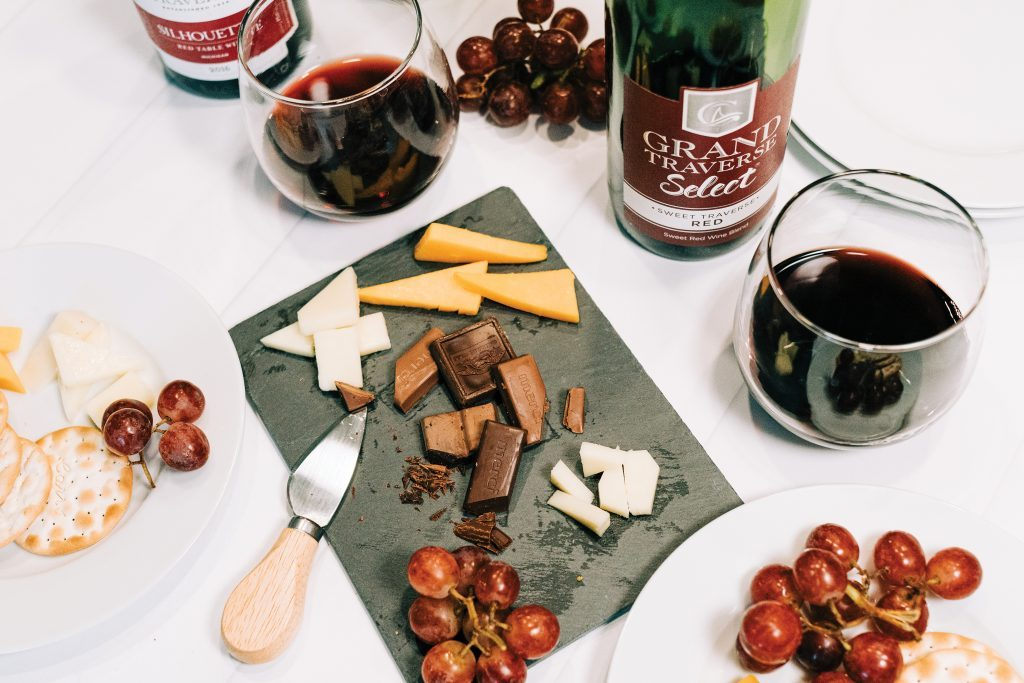 Charcuterie board with cheese, chocolate, grapes, and Chateau Grand Traverse wine