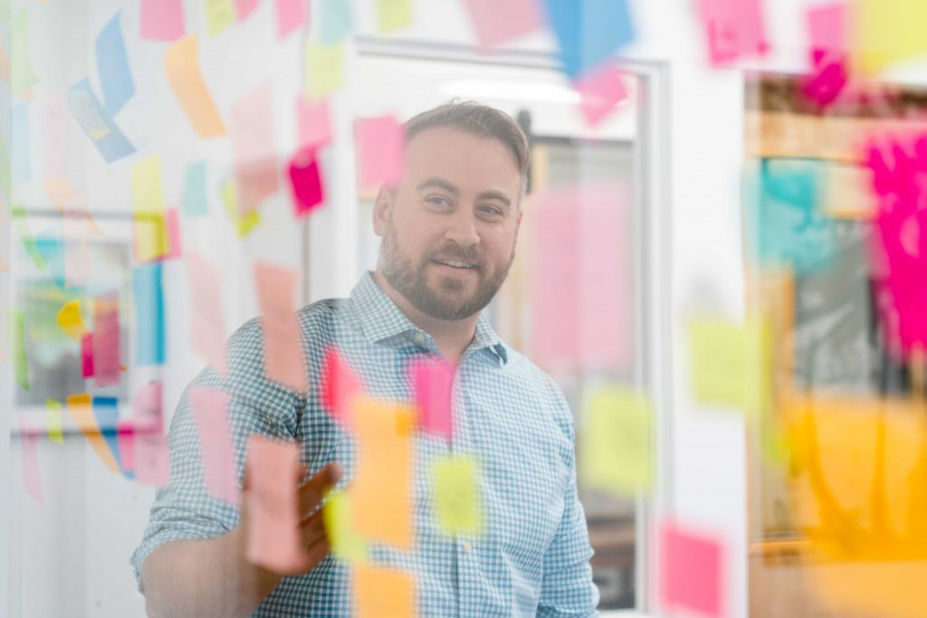 Looking through a window, seeing a man pointing at a wall of post-it notes during a brainstorming session at Oneupweb