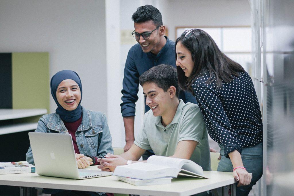 University students gather around laptop