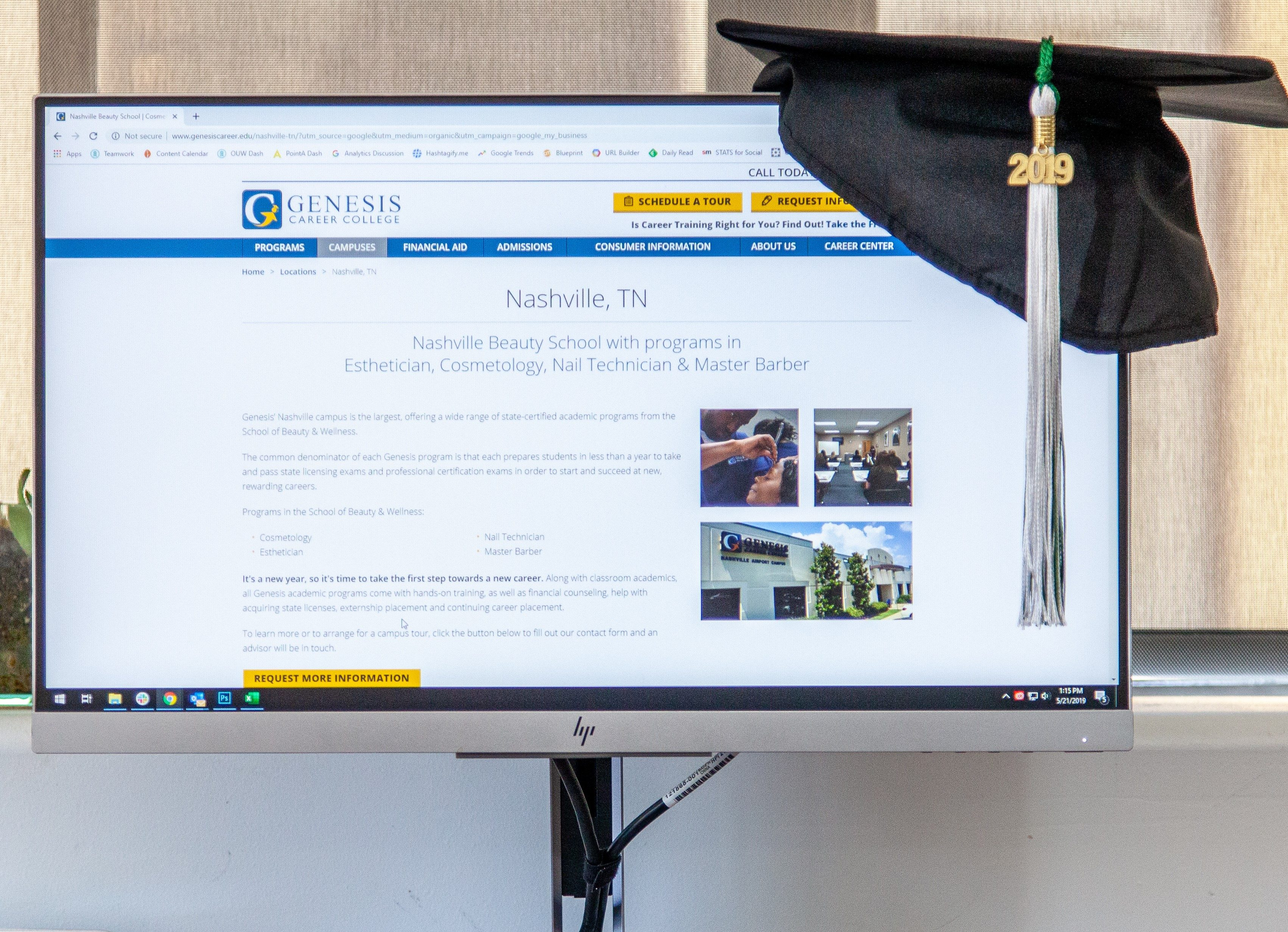 Genesis Career College website on a computer screen with a graduation hat on the corner