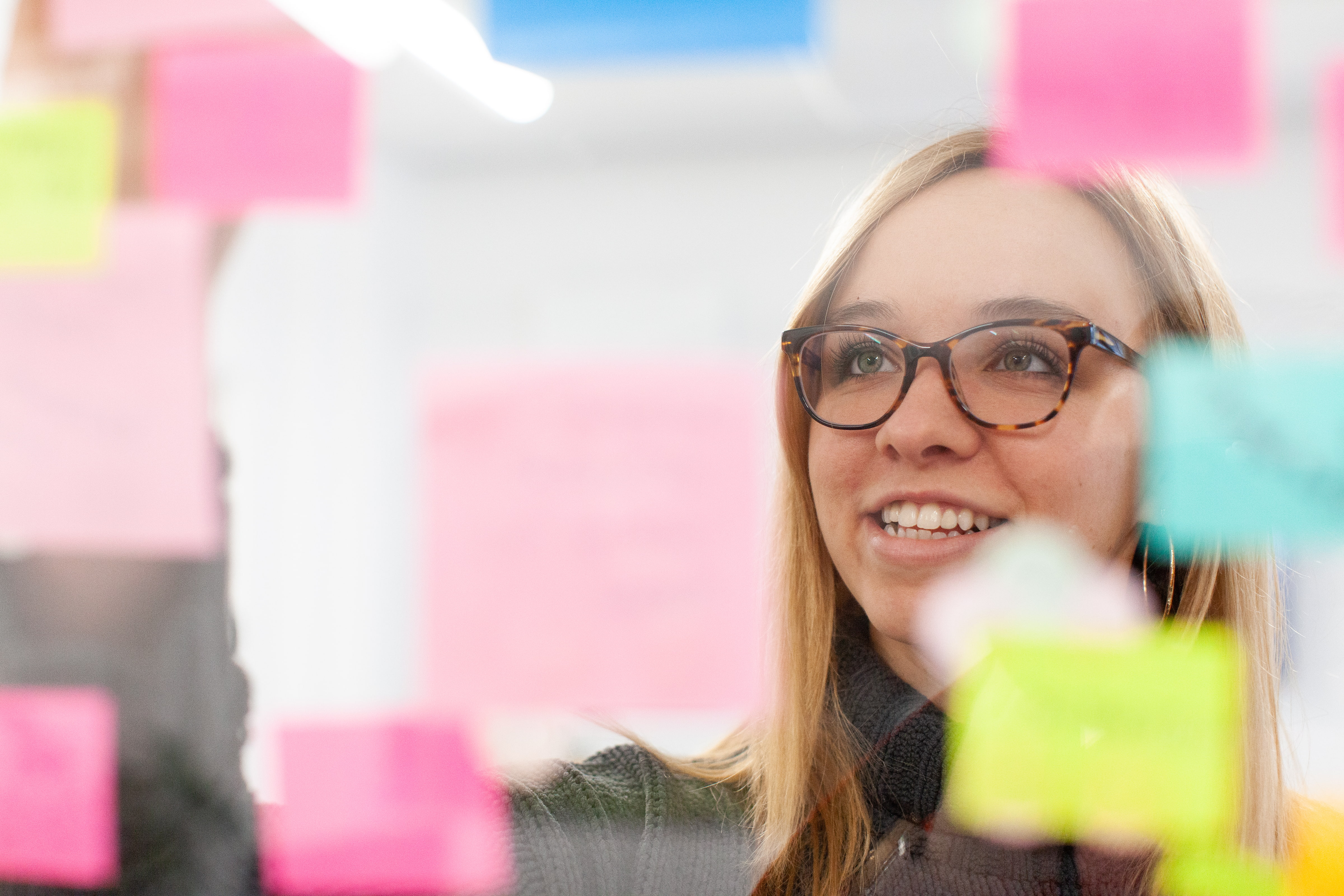 Woman reads sticky notes on a window to brainstorm marketing strategies