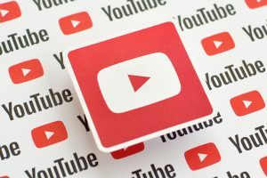 Youtube logo sticker on pattern printed on paper with small youtube logos and inscriptions. YouTube is Google subsidiary and American most popular video-sharing platform