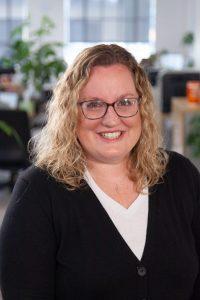 Headshot of Oneupweb employee smiling in office