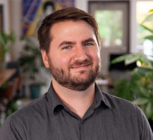 Headshot of Oneupweb male employee smiling in office
