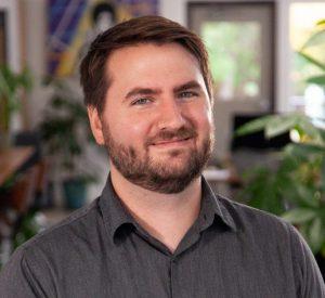 Headshot of Oneupweb male employee smiling in office