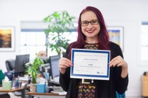 Oneupweb employee smiling while holding an ABA Professional Certification