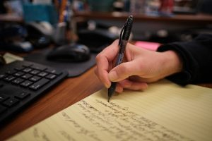 person writing cursive on yellow legal pad notebook next to work desk keyboard