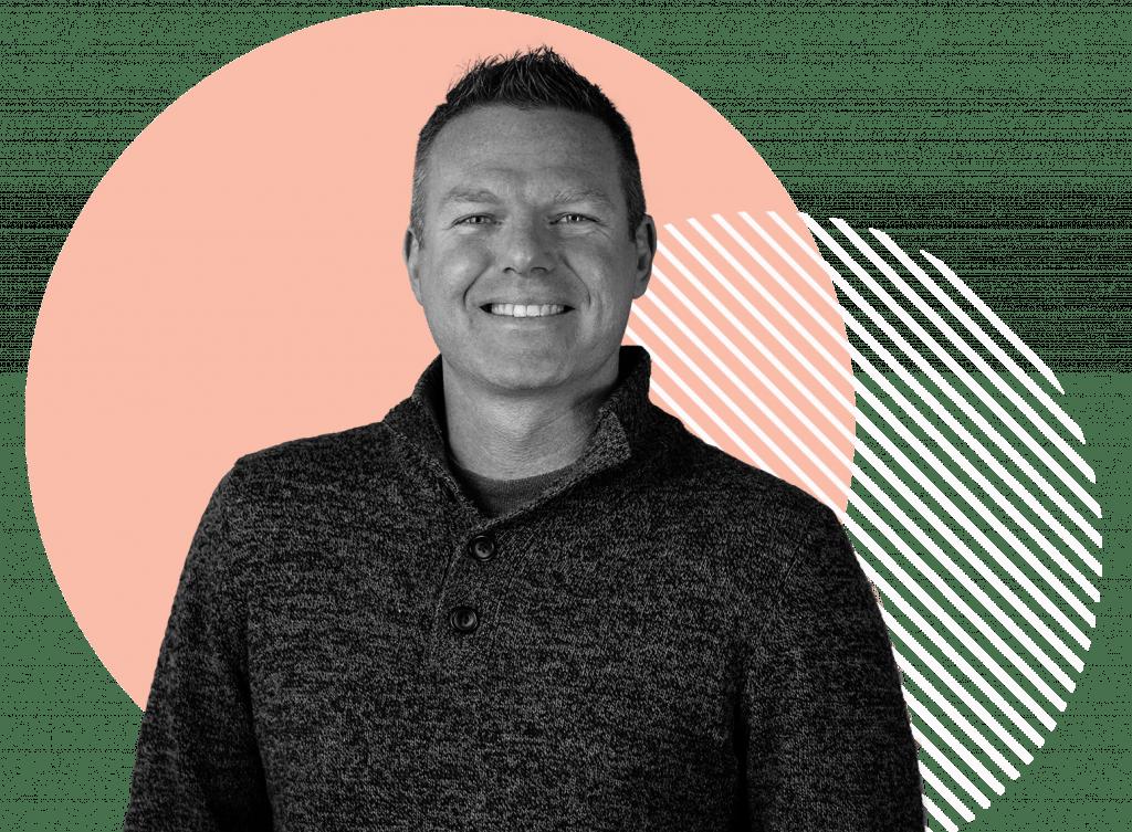 Shawn Finn, a Oneupweb employee, smiles while wearing a nice sweater