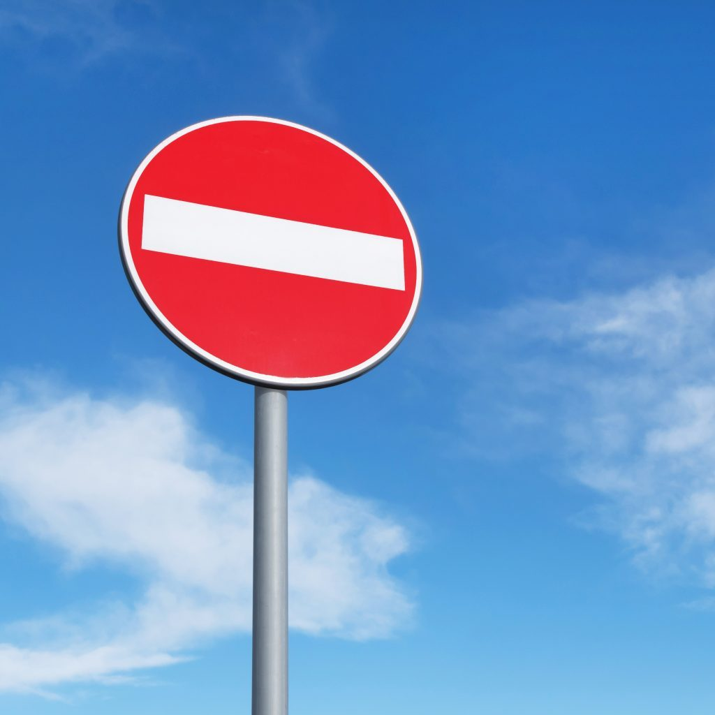 a do not enter symbol on a sign stands tall against a blue sky with white clouds