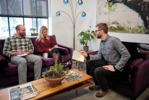 a man and a woman site on a purple couch, listening and taking notes while another man on a purple chair talks to them about a digital marketing budget in an office setting