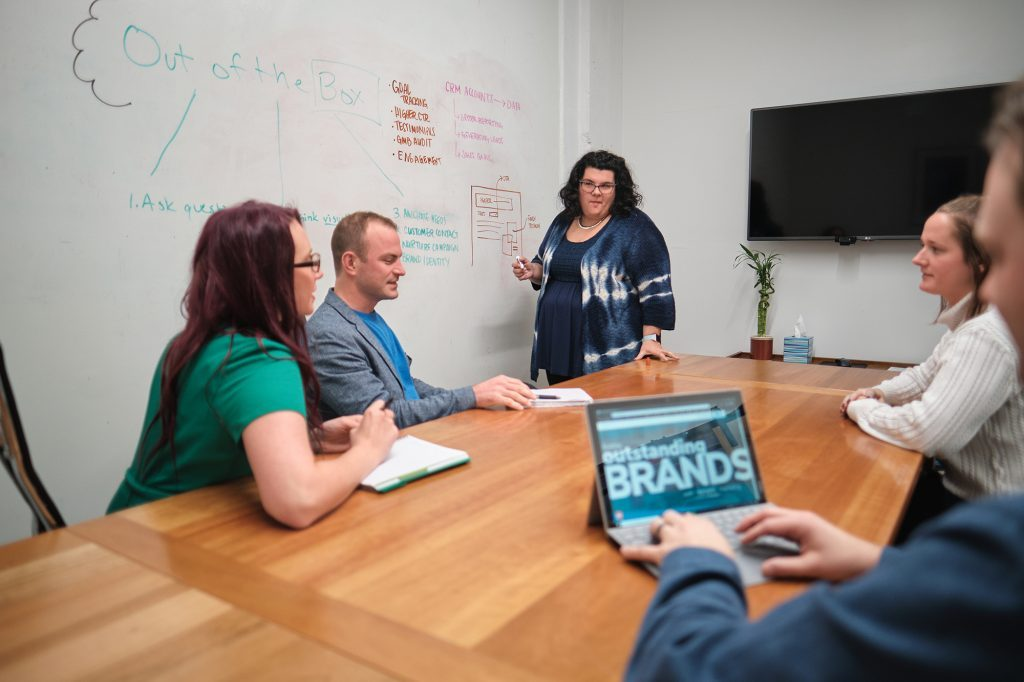 a team of marketers work in a conference room in front of a white board brainstorming ways to create new social media marketing campaigns