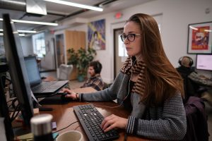 A female page experience expert works at a computer while wearing glasses and a scarf