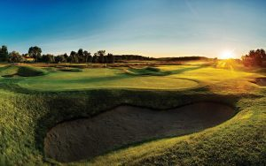 a photo of a golf course with sand and rolling hills as the sun peeks over the horizon in the evening on a clear day