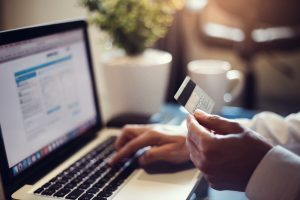 hands rest on a computer while holding a credit card prepared to make an online purchase from an ecommerce website