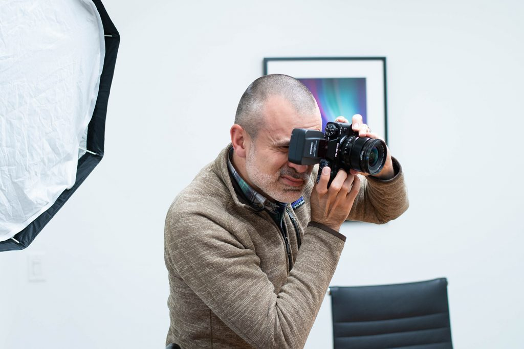 a man holds a digital camera up to his eyes to take a photograph while in an office setting