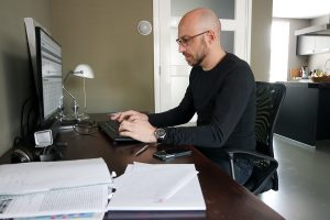 a man works at a home office desk, with papers scattered about, while writing a blog with seo tips