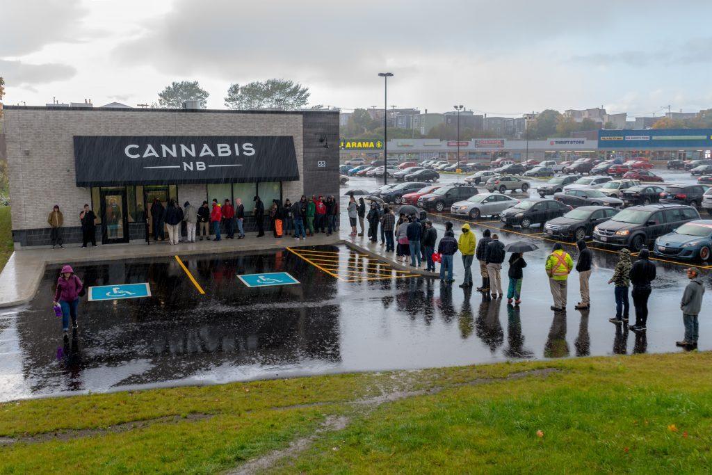 a line of customers wait to enter a marijuana dispensary