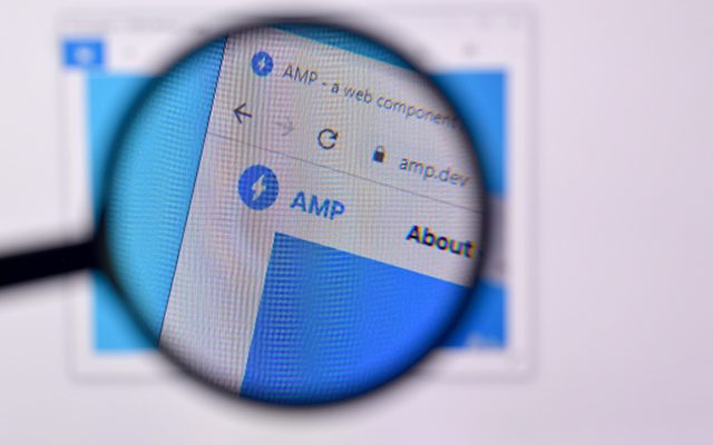 """a magnifying glass hovers over a computer screen showing """"amp"""" for accelerated mobile pages"""