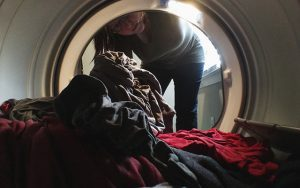 a look from inside a dryer pointing out at a woman taking clothes out